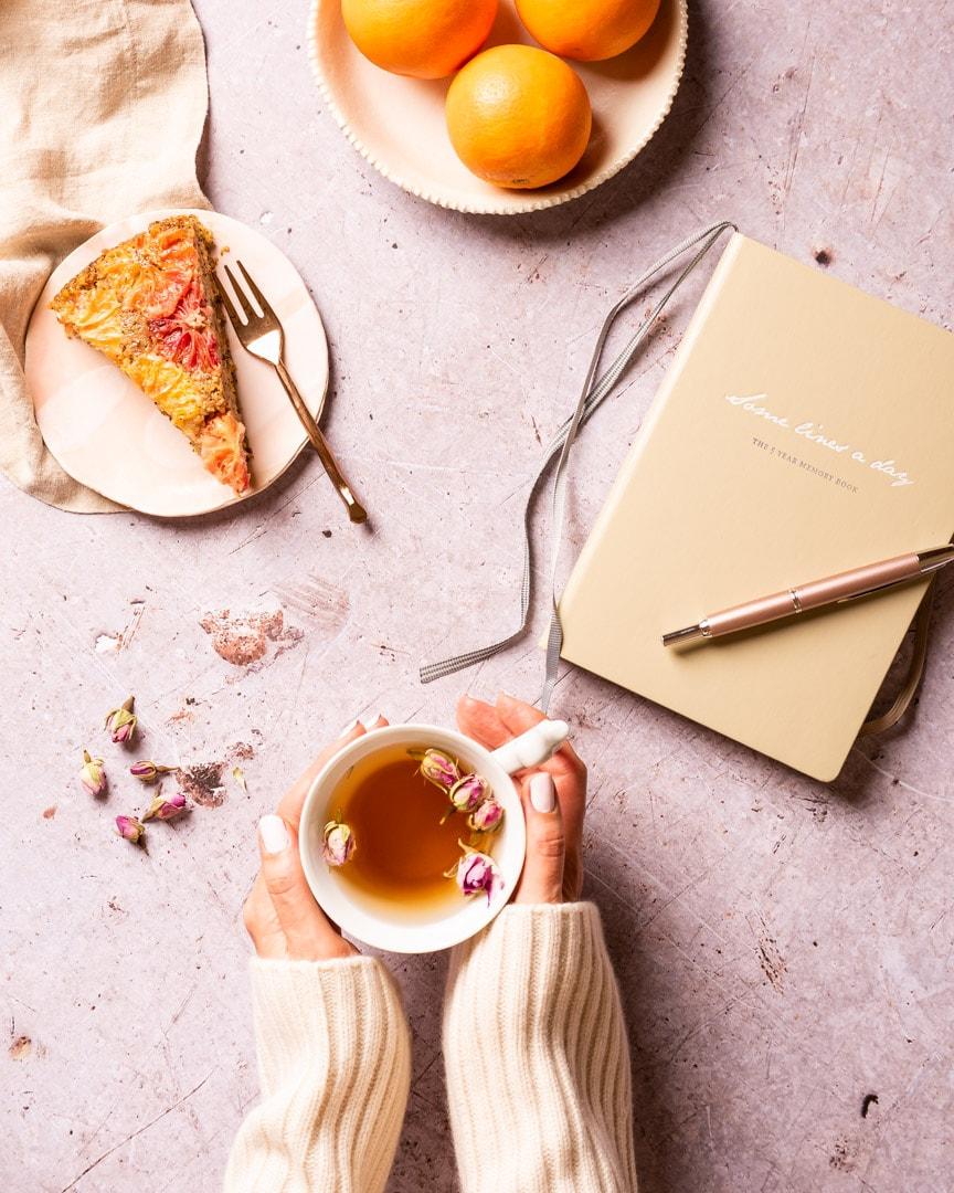 Rosebud tea wit diary and slice of blood orange cake and bowl of blood oranges