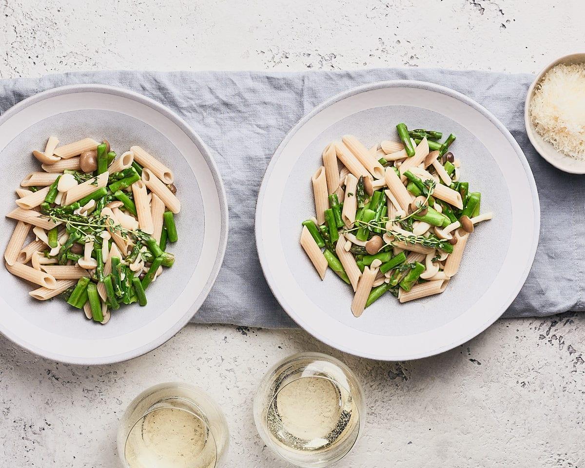 topdown view of 2 plates of asparagus mushroom pasta