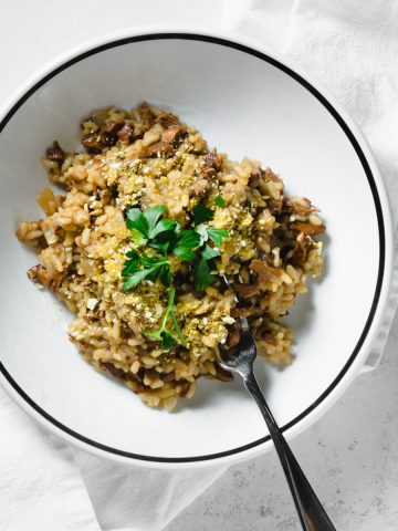 wild mushroom and leek risotto in bowl with fork