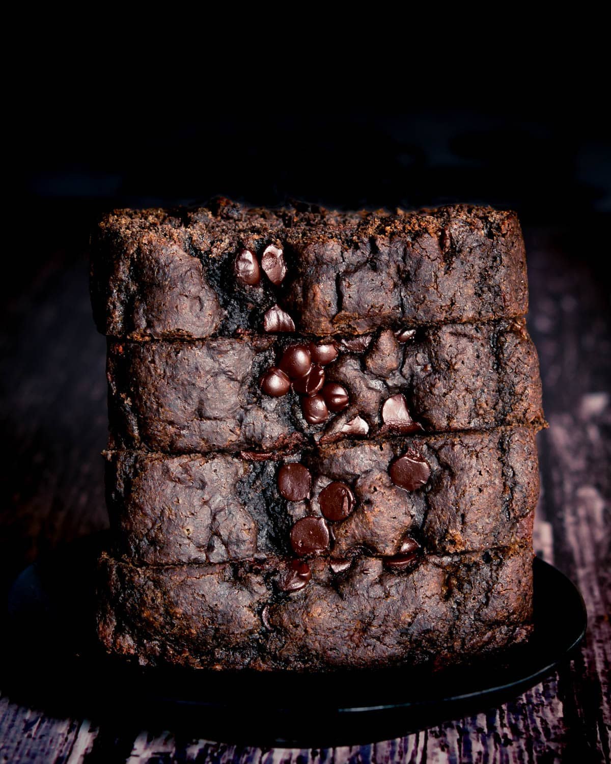 Stack of black tahini banana bread slices on black plate on wooden table close up