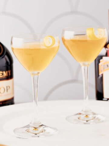 Sideview of 2 sidecar cocktails in coupe glasses