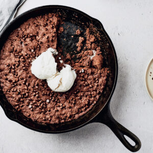 Overhead view of Vegan Peanut Butter and Chocolate Skillet Cookie with vegan vanilla ice cream
