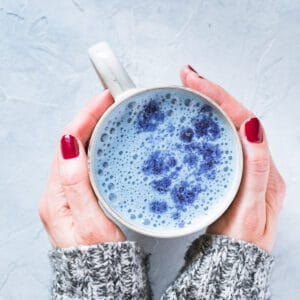 top view of hands holding butterfly pea latte