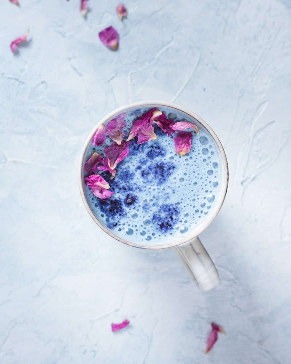 top down view of butterfly pea latte with rose petals