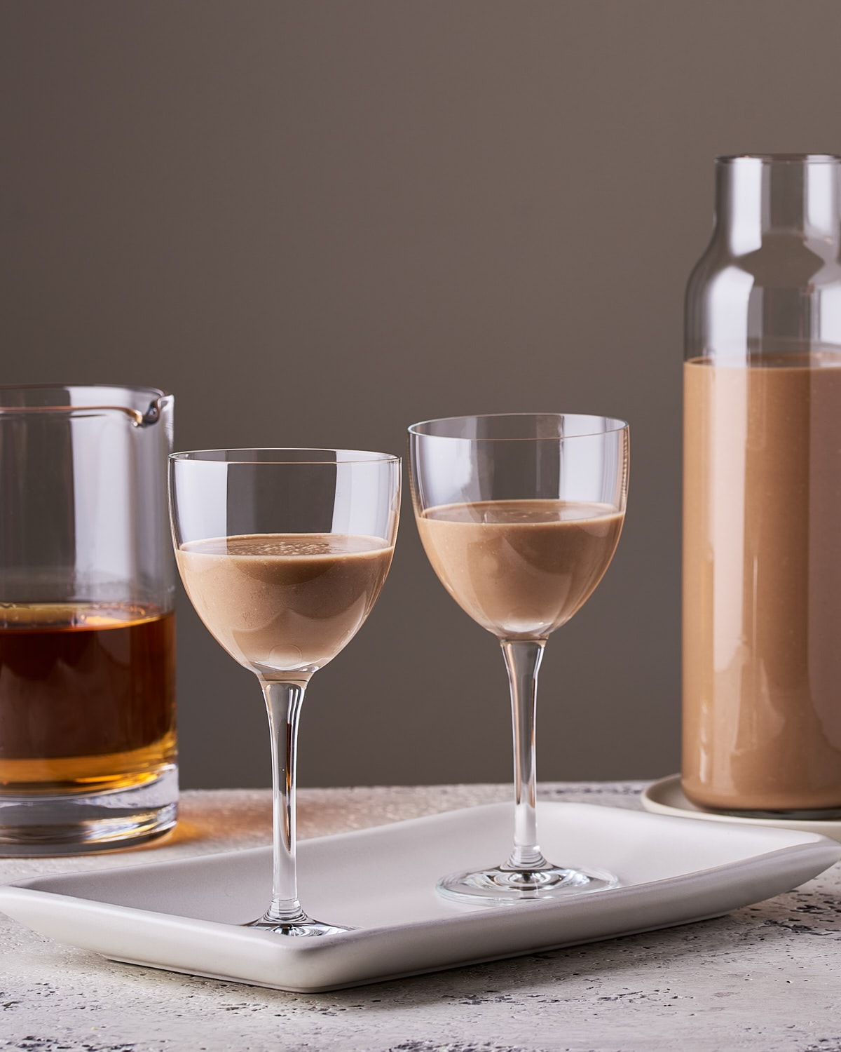 side view of 2 glasses of Irish cream with 2 glass bottles