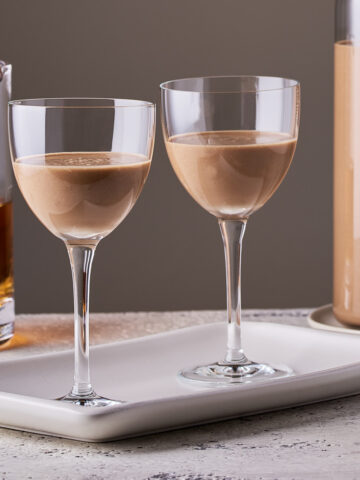 Side view of vegan Irish cream 2 glasses with 1 bottle and 1 pitcher