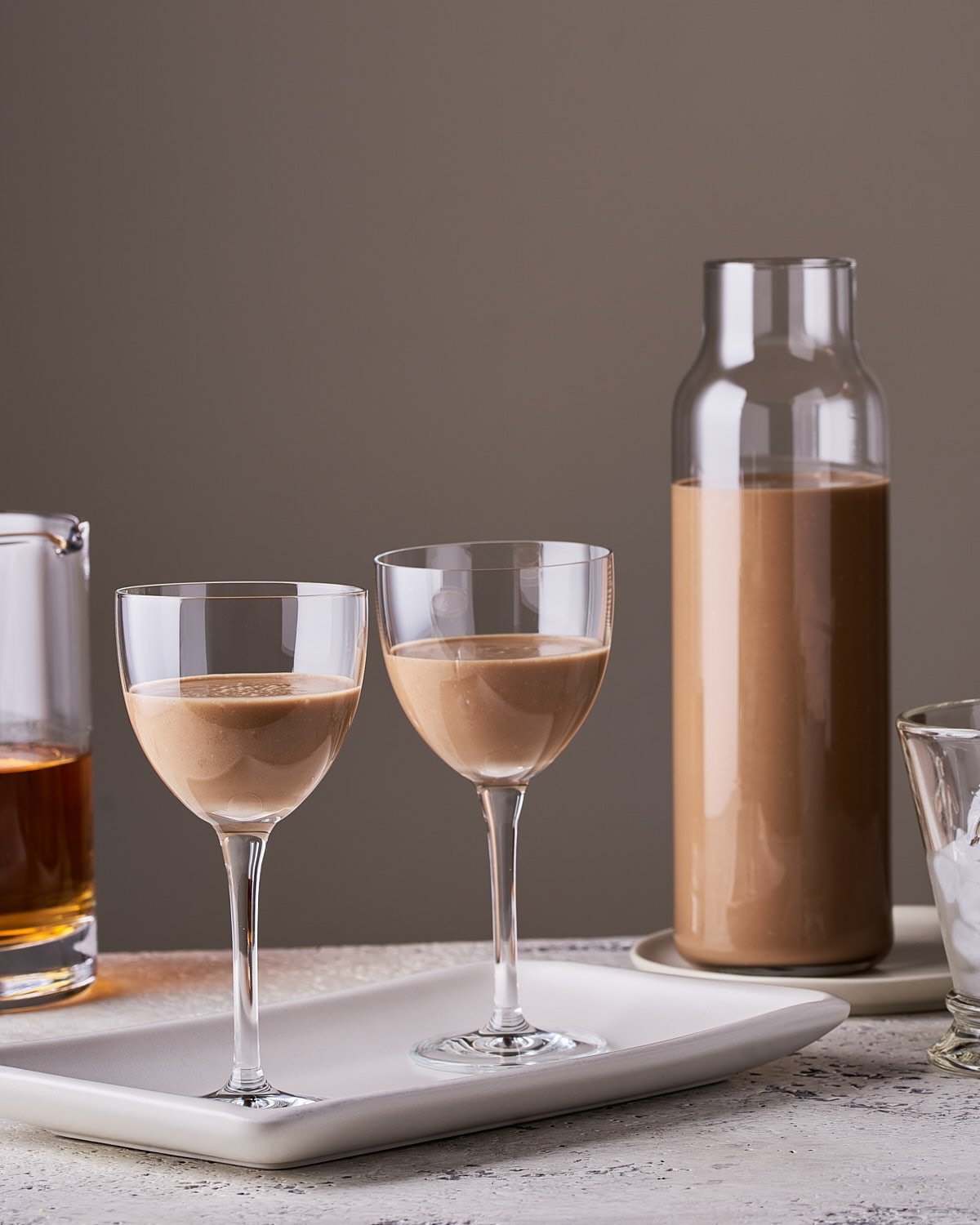side view of 2 glasses of vegan Irish cream with glass bottle and pitcher