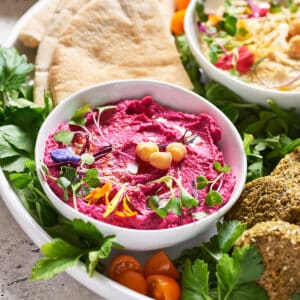 Side view of pink hummus in white bowl on platter