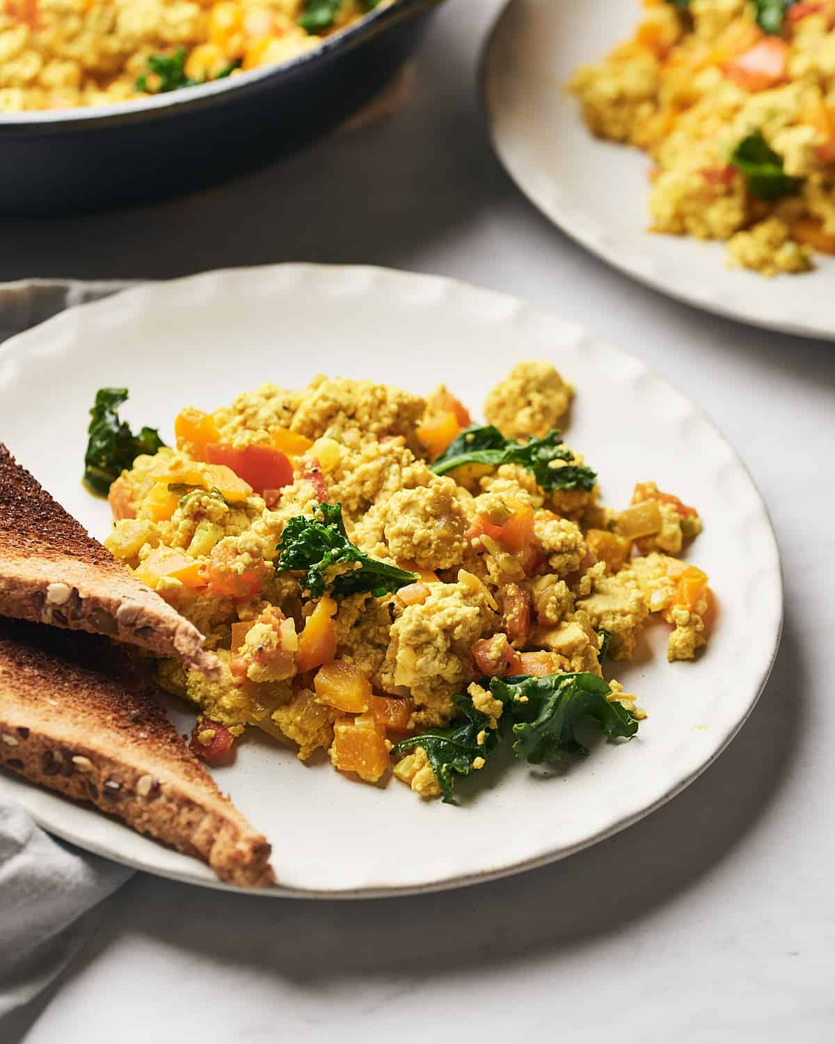 side view of scrambled tofu on plat with toast