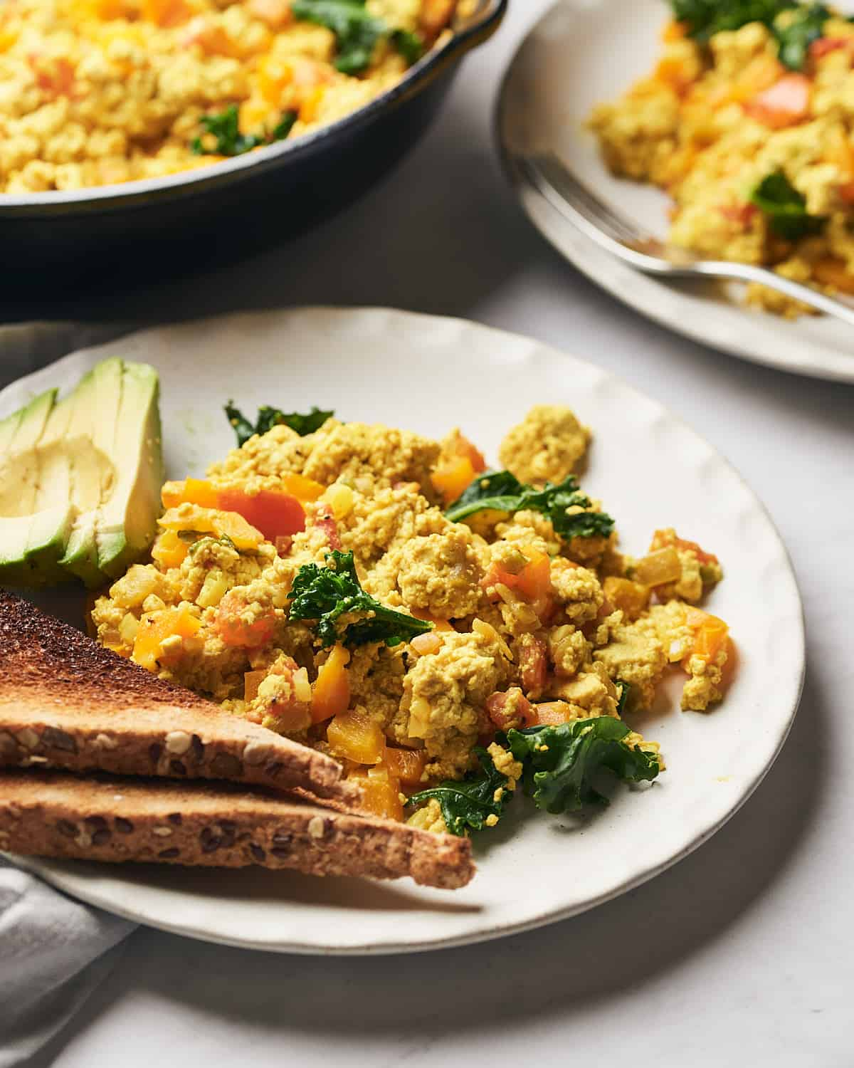 Side view of scrambled tofu on plate with toast and avocado