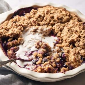 side view of healthy gluten-free vegan blueberry cobbler in pie dish