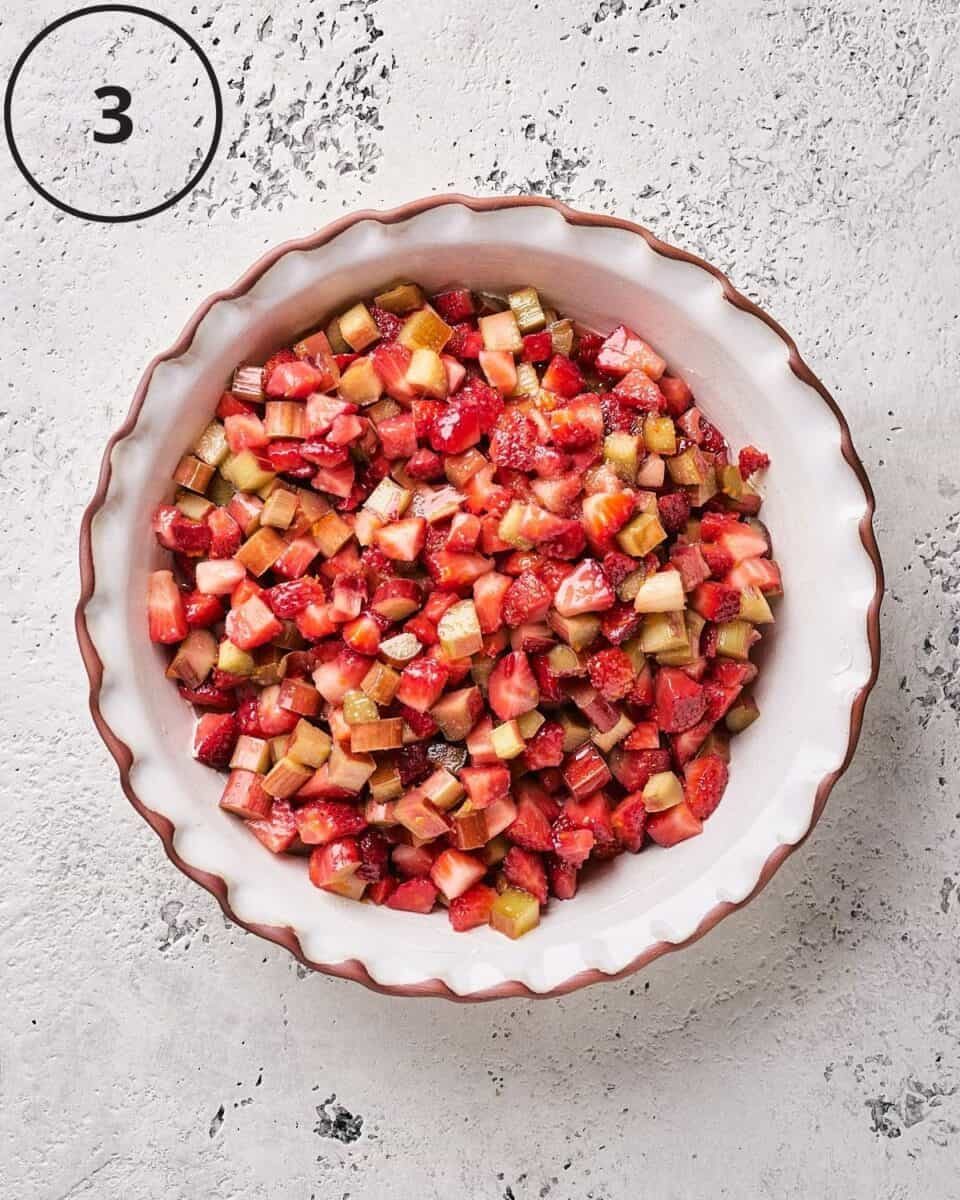 fresh fruit and sugar combined with arrowroot powder and orange juice in deep pie dish in overhead shot