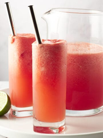 Side view of two glasses of watermelon coolers with pitcher on a white round plate