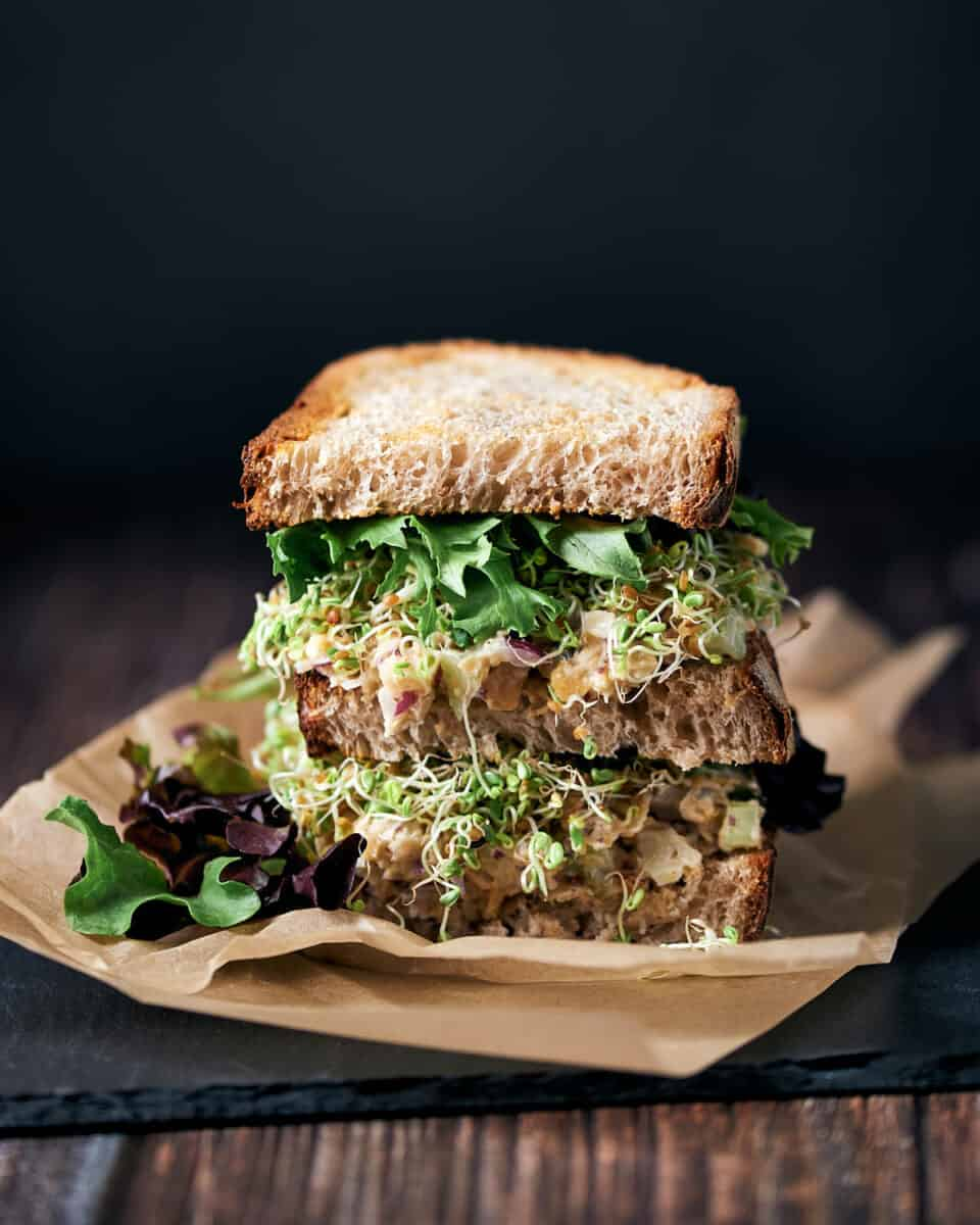 Side view of stacked chickpea salad sandwich with sprouts and spring mix on parchment paper