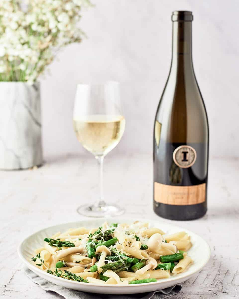 Plate of vegan asparagust mushroom pasta with bottle and glass of white wine with white and green flowers in background