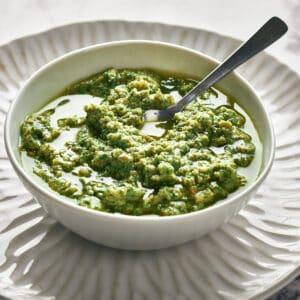 easy vegan basil pesto in white bowl with spoon on white plate