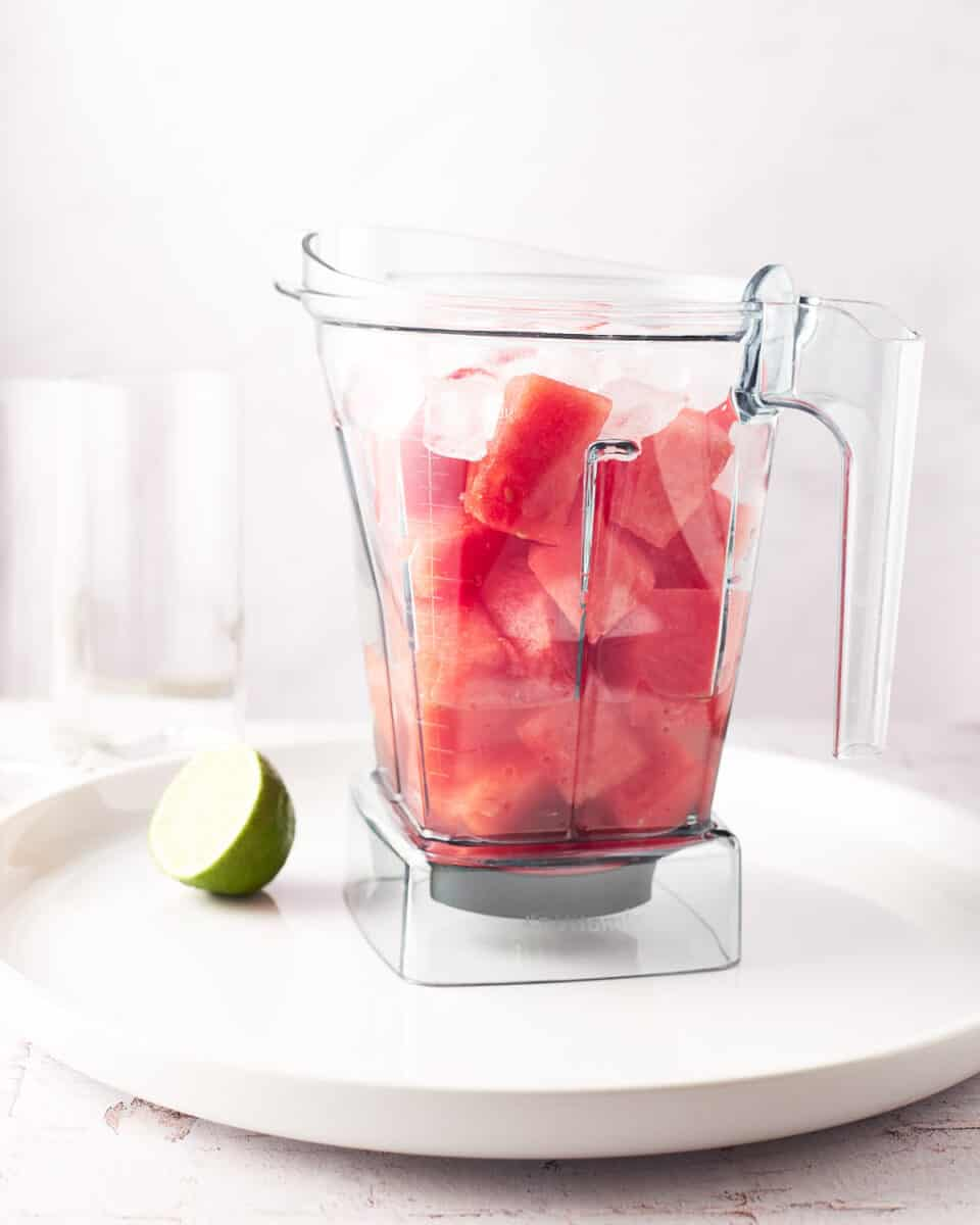 Kitchenaid blender filled with cut watermelon chunks on a white platter