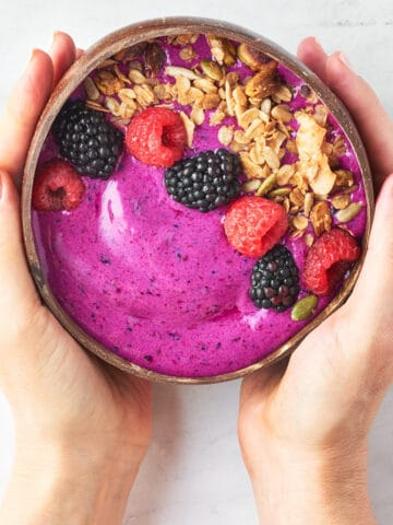 overhead view of hands holding dragonfruit smoothie bowl with granola, fresh berries with marble background