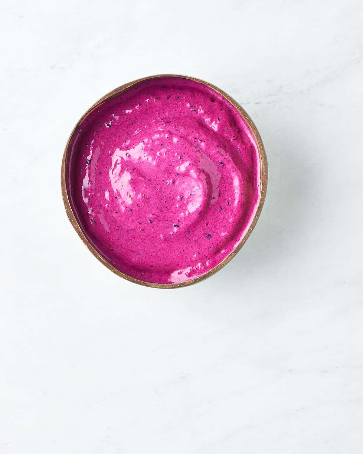 Overhead view of Dragonfruit Smoothie Bowl on a marble background
