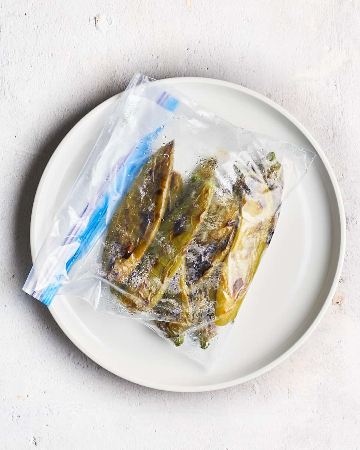Top down view of Hatch Chiles steaming in a plastic bag on a white plate_Resplendent Kitchen