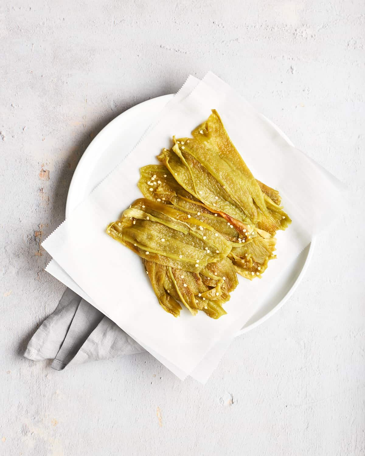 Peeled and seeded roasted Hatch chiles on a white plate on concrete background_Resplendent Kitchen