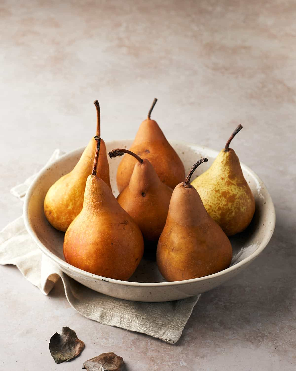 Six bosc pears in a bowl with a beige napkin