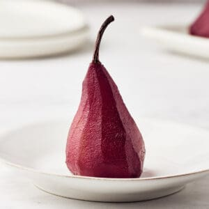 poached pear in red wine on a white plate
