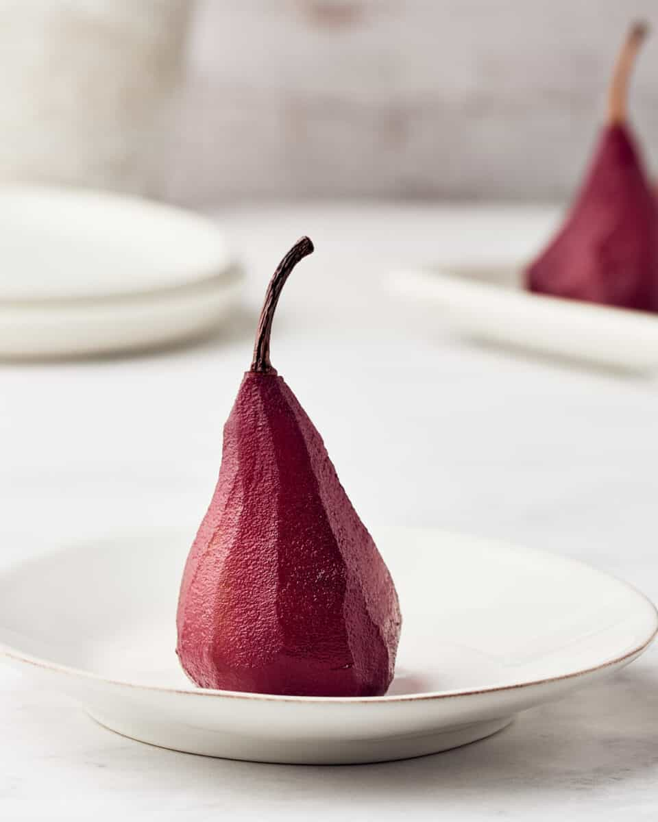 poached pear in red wine on a white plaate on a marble background