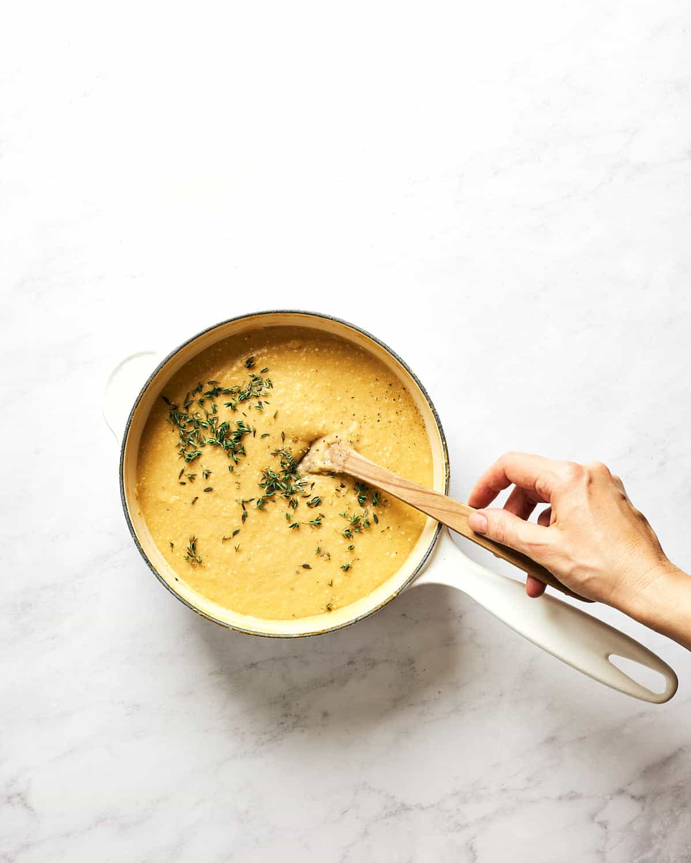 Stirring creamy polenta with thyme